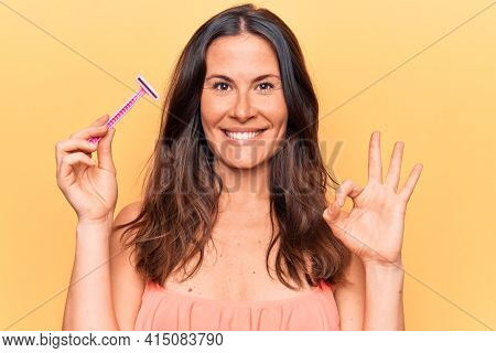 Beautiful brunette woman asking for depilation holding shaver razor over yellow background doing ok sign with fingers, smiling friendly gesturing excellent symbol