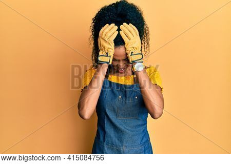 Middle age african american woman wearing professional apron suffering from headache desperate and stressed because pain and migraine. hands on head.