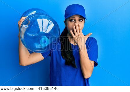 Young hispanic woman wearing delivery uniform holding water carafe covering mouth with hand, shocked and afraid for mistake. surprised expression