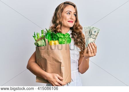 Young blonde girl holding paper bag with groceries smiling looking to the side and staring away thinking.