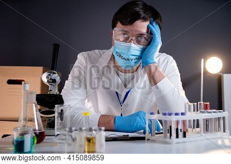 Exhausted Doctor In Medical Mask With Inscription Coronavirus On It. The Medical System Is Failing,