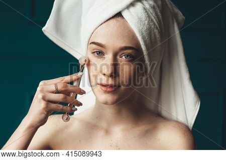 Caucasian Ginger Woman With Freckles Is Massaging Her Face With A Derma Roller Looking At Camera Wit