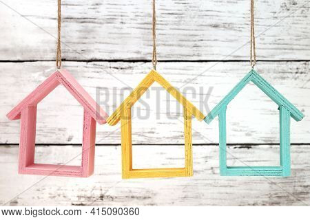 Wooden Miniature Houses Hanging By Strings On White Grunge Wall