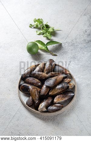 Shellfish Raw Mussels On Gray Plate, Gray Background. Shellfish Seafood. Top View.