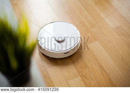Vacuum Cleaner Robot Runs On Wood Floor In A Office