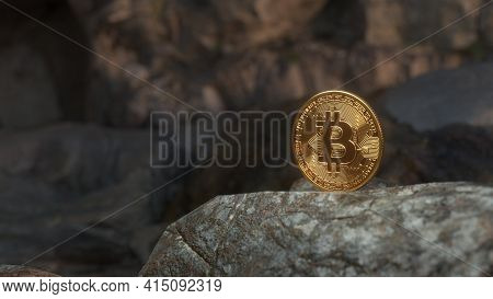 Golden Bitcoin Standing On Stones On Dark Mountains Background. Crypto Currency Blockchain. For Back