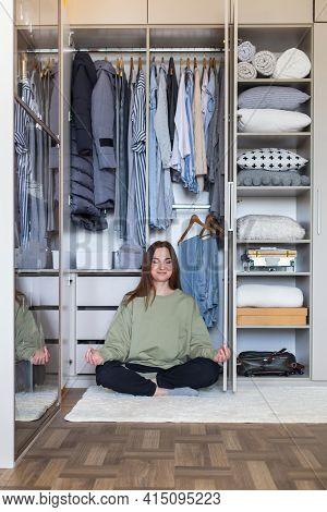 Cheerful Female In Lotus Position At Modern Wardrobe Storage. Happy Housewife Posing Meditating
