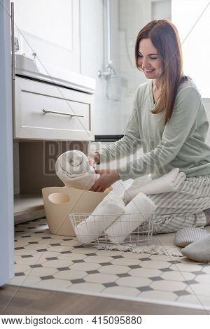 Smiling Housewife Rolled Up Bath Towel Organizing Storage In Closet Under Sink. Marie Kondos Method
