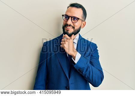 Young man with beard wearing business suit and tie with hand on chin thinking about question, pensive expression. smiling with thoughtful face. doubt concept.