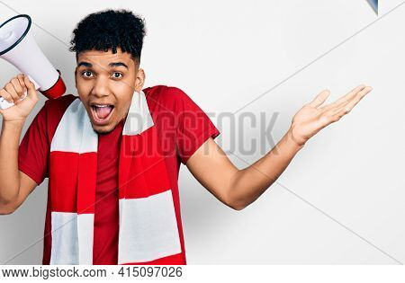 Young african american man football hooligan holding megaphone celebrating victory with happy smile and winner expression with raised hands