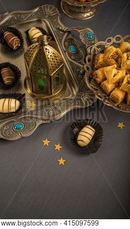 Beautiful photo background for Ramadan and Eid festival celebration. Arabic traditional sweet, premium date chocolate served on an ornamental tray, placed with Arabic lamp.
