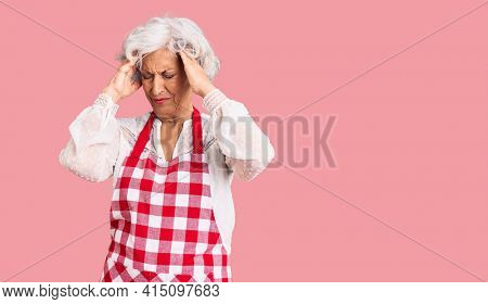 Senior grey-haired woman wearing apron suffering from headache desperate and stressed because pain and migraine. hands on head.