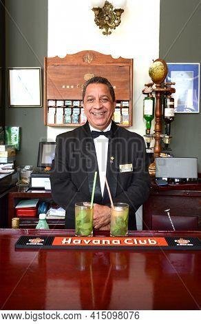 HAVANA, CUBA - JULY 21, 2016: Hotel Nacional de Cuba Bar. The Bartender stands behind two freshly made Mojito Cocktails.