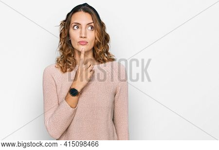 Beautiful young caucasian woman wearing casual sweater thinking concentrated about doubt with finger on chin and looking up wondering