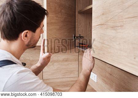 Man Open Kitchen Cupboard. Repairman In Uniform Fixing Cabinet At Kitchen