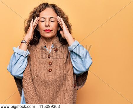 Middle age beautiful woman wearing casual sweater standing over isolated yellow background with hand on head, headache because stress. Suffering migraine.