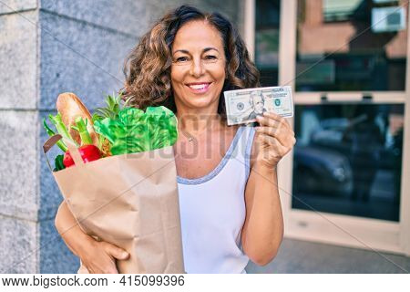 Middle age hispanic woman smiling happy holding a grocery shopping bag full of groceries and american 20 dollar at the city.