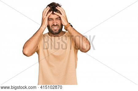 Handsome young man with beard wearing casual tshirt suffering from headache desperate and stressed because pain and migraine. hands on head.