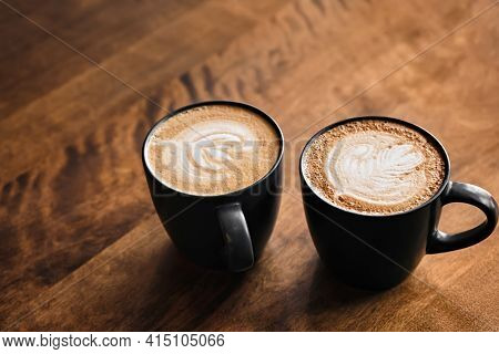 Two Cappuccino Coffee With Latte Art On Wooden Table. Black Cups And Beautiful Milk Foam. Soft Focus