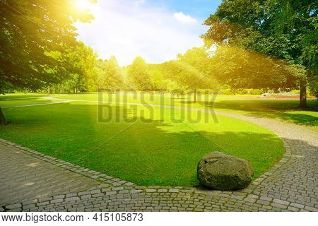 Bright sunbeams over beautiful meadow with green grass and walking paths in public park.