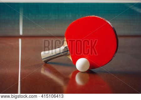table tennis racket and ball, net background