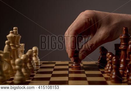 Male Hand Moving Pawn On Chess Board, Starting Game And Making First Step. Making Business Decision
