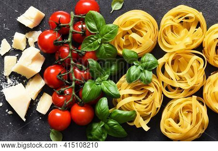 Tagliatele Pasta, Tomatoes, Basil And Parmesan Cheese On A Black Concrete Background. Ingredients Fo