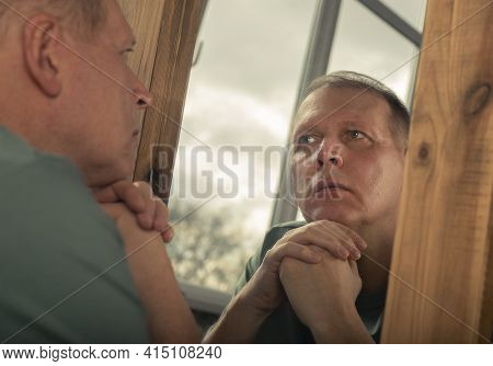 Middle-aged Man Looking At Mirror Reflection Seriously, Thinking About His Age And Life