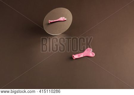 A Small Balloon In The Shape Of A Pink Heart With A Reflection In A Small Mirror. Brown Background.