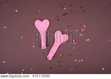 Two Small Balloons For Inflating Air And Helium In The Form Of A Heart. Pink Balls On A Brown Backgr