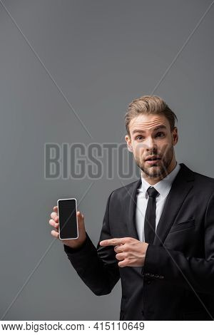 Discouraged Manager Pointing At Smartphone With Blank Screen Isolated On Grey.