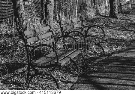 Grayscale Of Two Empty Benches In A Park, On A Sunny Day. Side Angle Shot. The Focus Is On The Left
