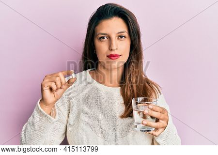 Beautiful hispanic woman holding pill and glass of water relaxed with serious expression on face. simple and natural looking at the camera.