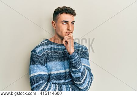 Hispanic young man wearing casual winter sweater thinking concentrated about doubt with finger on chin and looking up wondering
