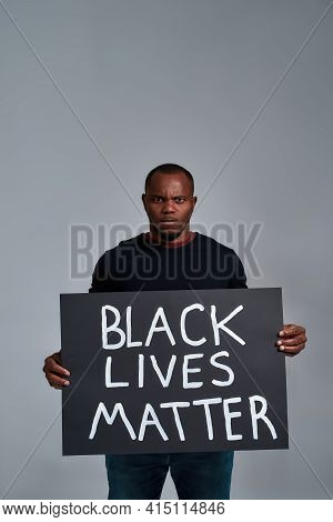 Strong African American Man Holding Anti Racism Placard And Looking At Camera While Posing On Light