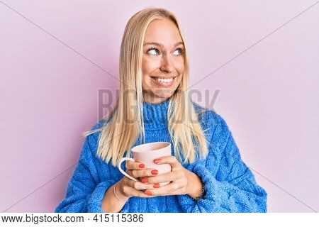 Young blonde girl wearing winter sweater and drinking a cup of hot coffee smiling looking to the side and staring away thinking.