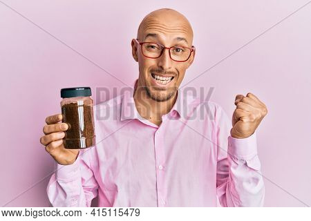 Bald man with beard holding soluble coffee screaming proud, celebrating victory and success very excited with raised arm