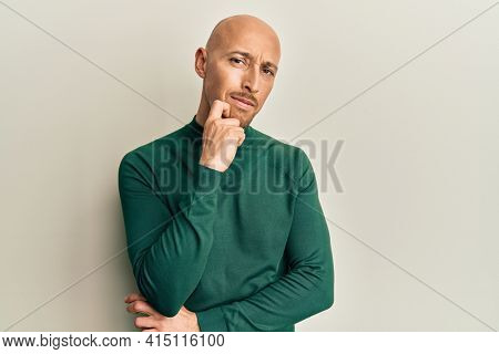 Bald man with beard wearing casual turtleneck sweater thinking concentrated about doubt with finger on chin and looking up wondering