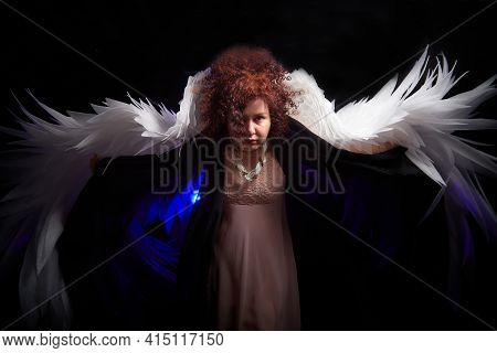 A Brunette Curly Girl In Black Dress Looking Like An Evil Angel With White Wings On A Black Backgrou