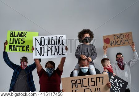 Young Multiracial Protestors And Little Kid Holding Anti Racist Posters And Wearing Buffs Standing O