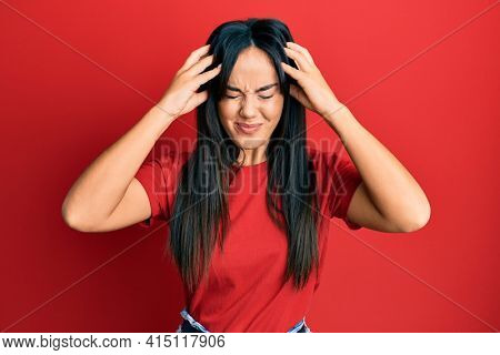 Young beautiful hispanic girl wearing casual red tshirt with hand on head, headache because stress. suffering migraine.