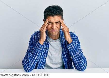 Young handsome african american man wearing casual clothes sitting on the table suffering from headache desperate and stressed because pain and migraine. hands on head.