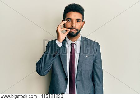 Handsome hispanic man with beard wearing business suit and tie mouth and lips shut as zip with fingers. secret and silent, taboo talking