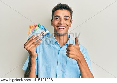 Young handsome african american man holding swiss franc banknotes smiling happy and positive, thumb up doing excellent and approval sign