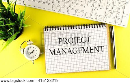 Project Management Text On Notebook With Keyboard , Pen And Alarm Clock On The Yellow Background