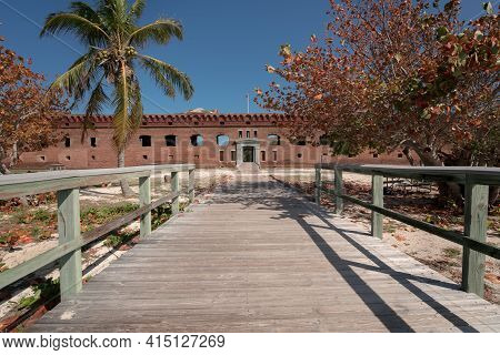 Gate Of An Old Military Fort With A Wooden Walk In The Foreground. Big Brick Walls And Green Palm Tr
