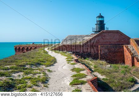 Old Black Lighthouse On A Rooftop Of Old, Civil War Military Fort In Florida. Ocean Horizon In The B