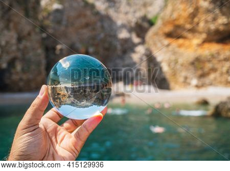 Crystal ball in the man's hand. Original upside down view and rounded perspective of the rocks and sea. Original and engaging picture.