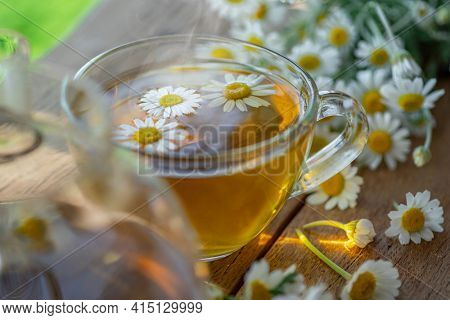 Herbal chamomile tea and chamomile flowers on wooden table. Close up.