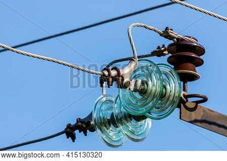Electric Pole Against The Blue Clear Sky. Three-phase Power Line To Turn.